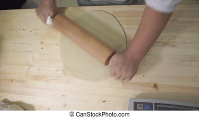 Baker on the desktop rolls the dough with a wooden rolling...