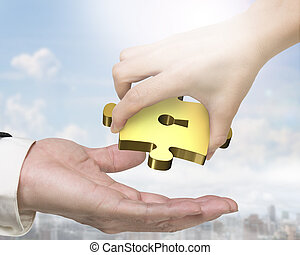 Hand giving one golden puzzle piece with keyhole - Female...
