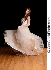 bride dancing in tulle dress with black background