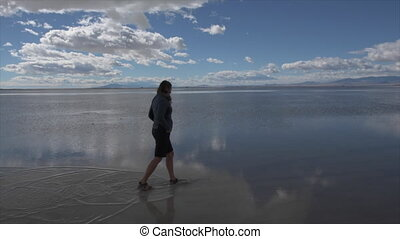 Bonneville Salt Flats Utah girl walking in shallow water -...