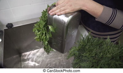 Woman pours water over the sink with a filled green container.