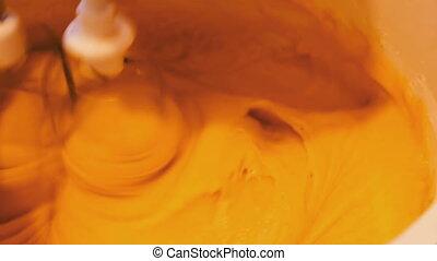 Mixer whisk dough for dessert - Yellow dough in a bowl that...
