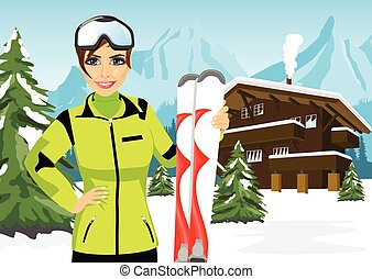 female mountain skier standing in front of chalet in winter...