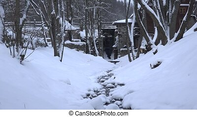 Snowy creek water flow in winter park channel. Snow fall....