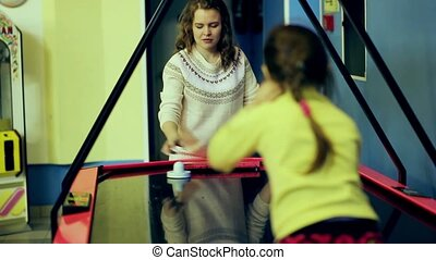 beautiful young girl enthusiastically playing air hockey in the room