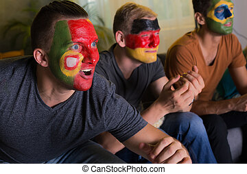 Excited football fans with colored faces - Three excited...