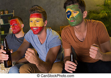 Friends with colored faces watching football - Group of...
