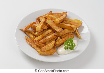 fried chipped potatoes - plate of chipped potatoes with...
