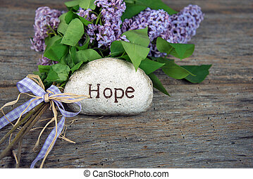 word hope on stone with lilacs