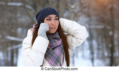 Young woman talking mobile phone and laughing in winter...