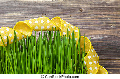 Green grass with yellow ribbon on rustic wooden background