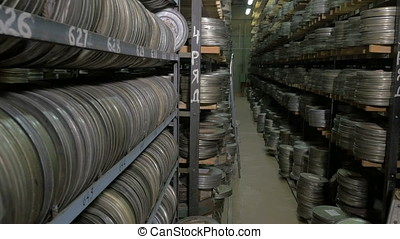 Vintage reel, video or audio tapes in a old media archives shelfs.