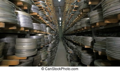 Old vintage film reel, film tapes in cases lying on archive...
