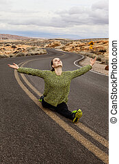 Young woman doing split on the road, USA