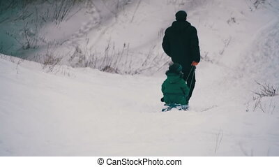 Man pulls a daughter sledding in the winter forest - Man...