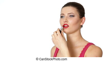 woman applying red lipstick on lips on white background.