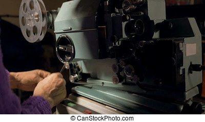 Worker set up antique Film Projector. - worker switch on...