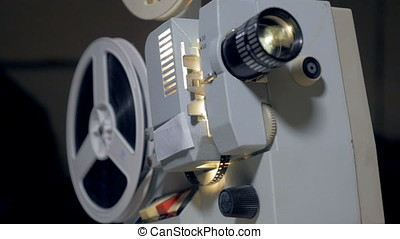 Vintage, old film projector with turning reels.