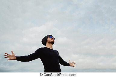 Cool handsome guy with his arms extended with the sky of...