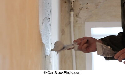Man plastering wall with spatula