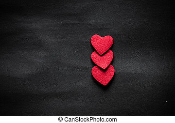three red hearts on black paper