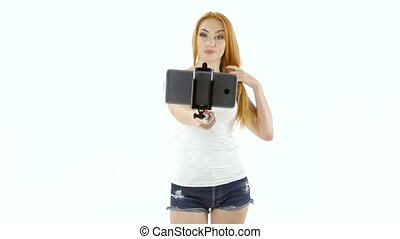 Redheaded model posing in front of a camera phone. Selfie -...
