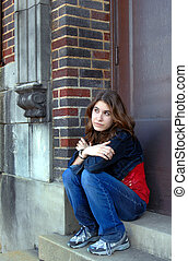 Lost in Thought - Young high school student sits on the...