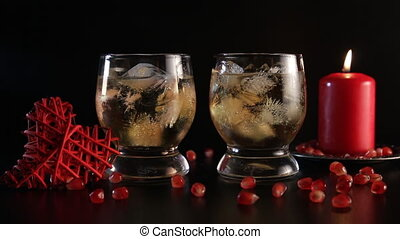 Two glasses with alcohol and ice, decorated with pomegranate, red candle and handmade heart, close-up. Romantic still life isolated on black background. Long shot. Saint valentine's day celebration.