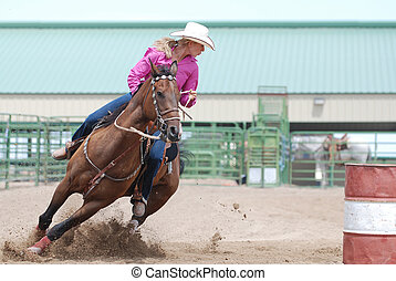 Barrel Racer - beautiful young woman riding a horse in a...