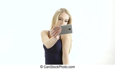 Blonde model looks poses for selfie photos on phone. Studio...