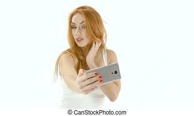 Redheaded girl model makes selfie photo on the mobile....