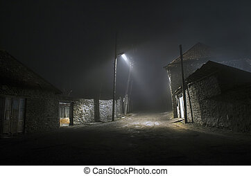 Night street country road with buildings and fences covered in fog lamp . Or Mysterious night in the centre of ?lisu village Gakh, Azerbaijan
