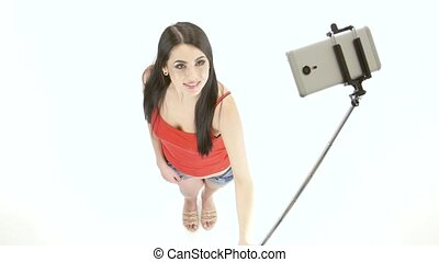 Brunette girl doing selfie photos using a monopod. White...
