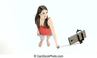 Girl doing selfie photos using a monopod. White background -...