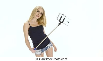 White background. Blonde makes photo on mobile using selfie...
