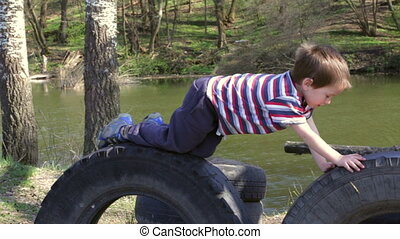 Two kids playing together on tires in playground - Two kids...