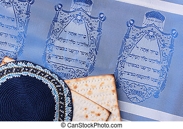 Jewish symbols - A blue kippah next to matzah and a Jewish...