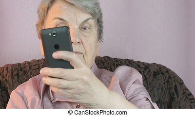 Aged woman 80s taking selfie using mobile phone - Aged woman...
