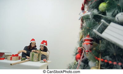 Two women prepare new year presents for Christmas holidays in office