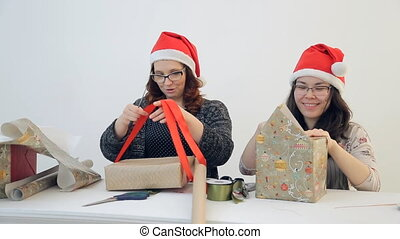 Two charming women pack Christmas gifts. Cute brunette in...