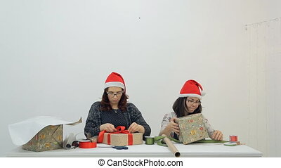 Two women decorate gifts with ribbons for Christmas, New Year.