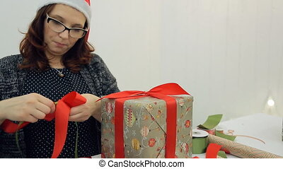 Woman makes bow gifts for Christmas, New Year. Female with...