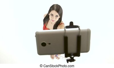Brunette girl doing selfie photos using a smartphone and...