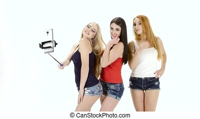 Brunette, redhead and blonde girl make selfie photo. White...