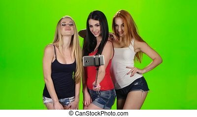 Three girl model pose for selfie photo. Green screen studio...