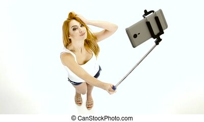 Redheaded girl doing selfie photos using a smartphone and...