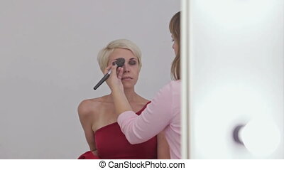 Professional make-up artist applying powder to womans face...