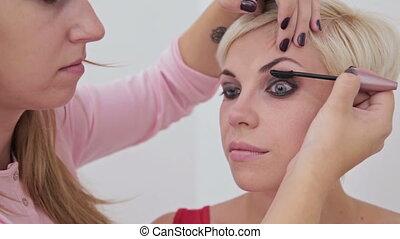 Professional make-up artist applying mascara on eyelashes of...