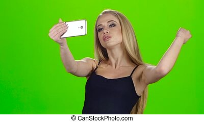 On the smartphone camera blonde girl doing selfie. Green...