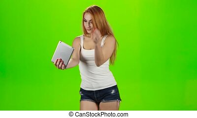 Redheaded girl model makes selfie on the tablet. Green screen